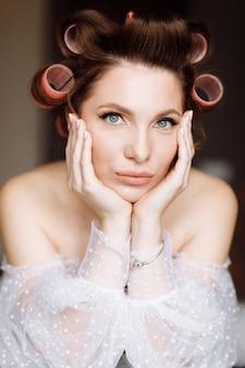 Красивая молодая эффектная брюнетка с ярким макияжем в стиле пин-ап в длинном белом кружевном платье и розовых бигуди.