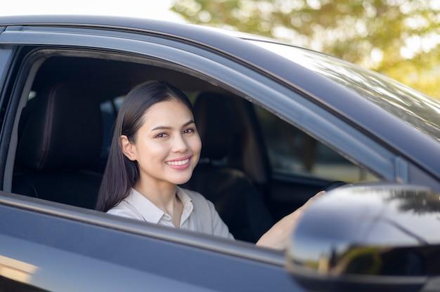 그녀의 차, 보험 및 금융 개념을 운전하는 아름 다운 젊은 웃는 여자