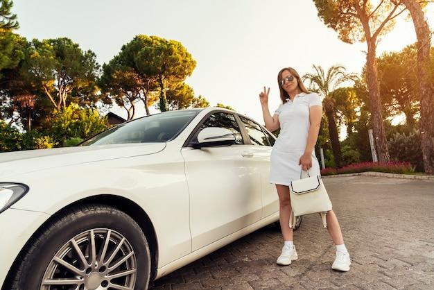 Красивая молодая успешная богатая женщина позирует возле своей дорогой машины, показывая знак победы с ...