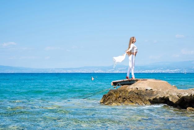 夏の海で風と気候を楽しむ美しい若い女性。