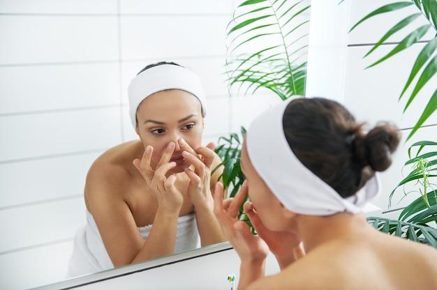 美しい若い女性が鏡の前で顔を調べます。毎朝の日課