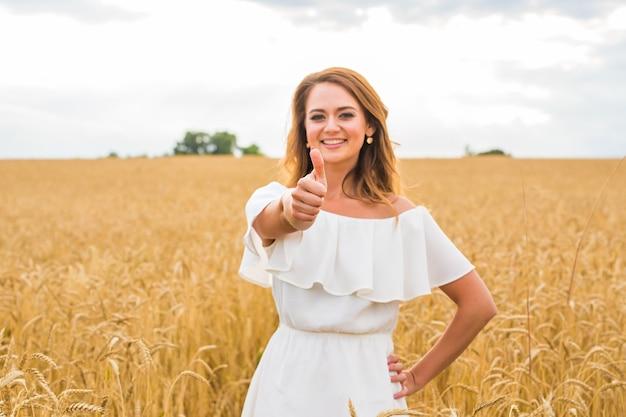 青い空の野原で親指を立てて笑っている美しい若い女性。
