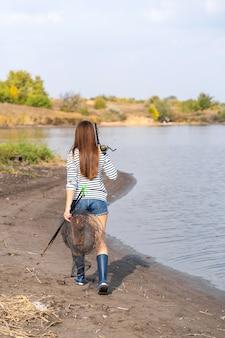 美しい若い女性が釣りに行きます。手に釣り竿とケージを持つ女性が湖に沿って歩いています