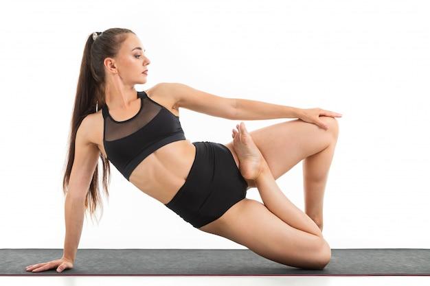 暗い長い髪の美しい若い女性の体操選手は、ウォームアップし、彼女の筋肉を伸ばす