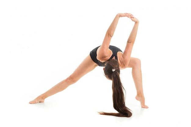 長い黒髪の美しい若い女性の体操選手は、ウォームアップをし、彼女の筋肉を伸ばし、ジャンプします。