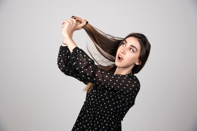Красивая молодая женщина держит ее здоровые и блестящие волосы.
