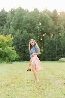 Красивая молодая женщина держит в руках летние туфли и ходит босиком по траве в летний день