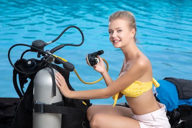 ビキニ姿の美しい若い女性がダイビング器材の近くに座っています