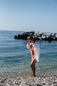 晴れた日には、ビキニ姿の美しい若い女性が巨大な岩を背景に海岸沿いを歩きます。観光と観光旅行。