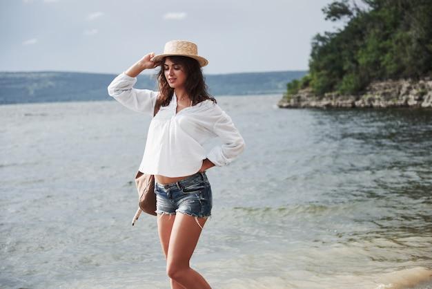 모자와 배낭에 아름 다운 젊은 여자는 장난스럽게 물에 의해 걷는다. 따뜻한 여름날은 자연의 모험과 모험을위한 좋은 시간입니다.
