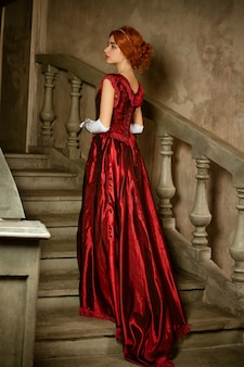 Красивая молодая женщина в длинном красном ретро платье стоит на лестнице