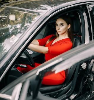 Красивая молодая женщина в красном комбинезоне сидит за рулем черной машины на пустой дороге в лесу
