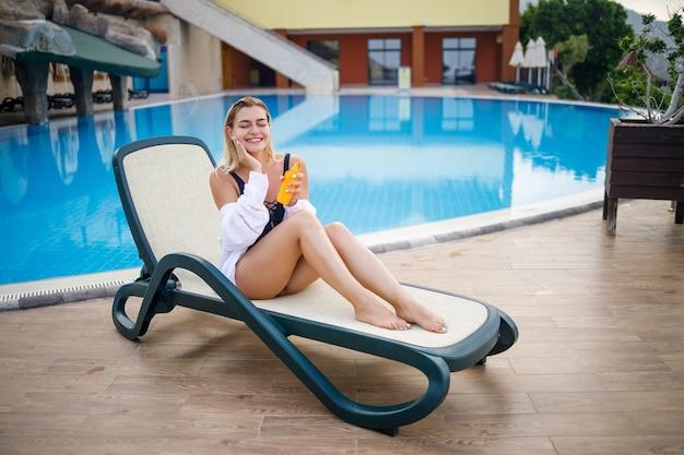 Красивая молодая женщина в купальнике и белой рубашке сидит на шезлонге у бассейна и натирает свое тело солнцезащитным кремом. летний уход за кожей, защита от ожога кожи