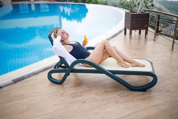 수영복과 흰색 셔츠를 입은 아름다운 젊은 여성이 수영장 옆 일광욕용 긴 의자에 앉아 선크림으로 몸을 문지릅니다. 여름 피부 관리, 피부 화상 방지