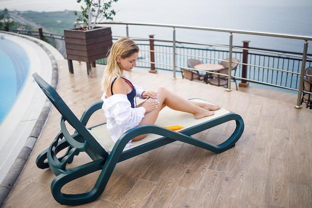 水着と白いシャツを着た美しい若い女性がプールサイドのサンラウンジャーに座って、日焼け止めで体をこすります。夏のスキンケア、皮膚のやけどに対する保護