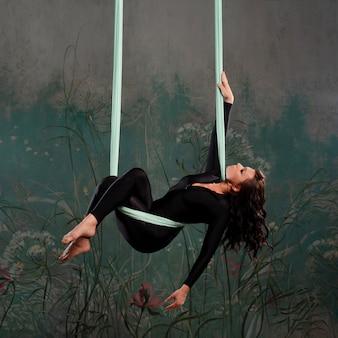 Красивая молодая женщина в обтягивающем черном спортивном костюме занимается йогой на подвесе