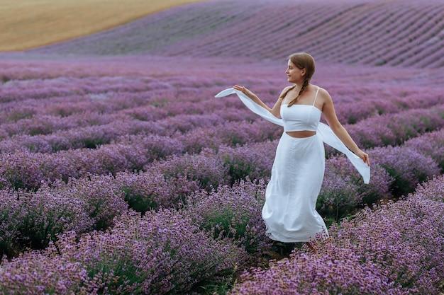 Красивая молодая женщина в белом платье и шляпе идет по лавандовому полю