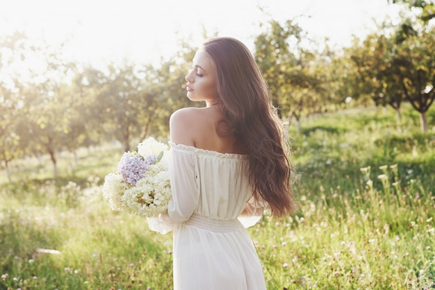 하얀 빛 드레스와 여름 꽃의 꽃다발에서 아름 다운 젊은 여자는 정원에서 좋은 하루를 낳는다