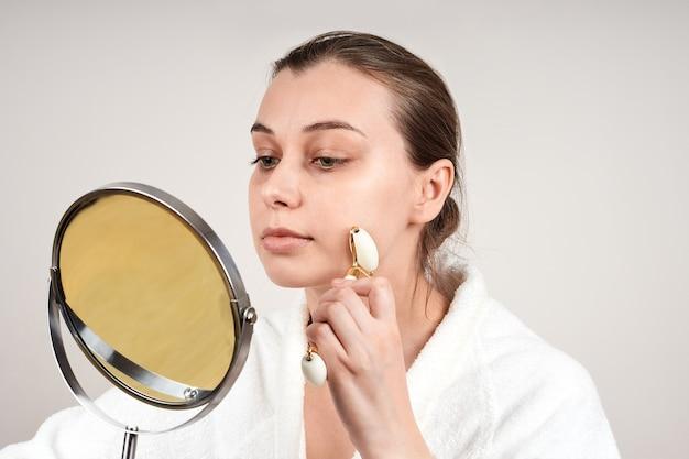 白いローブを着た美しい若い女性は、翡翠のロールを使用して顔をマッサージし、鏡を見る
