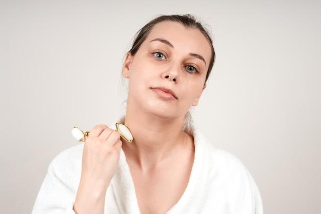 。白いローブを着た美しい若い女性は、翡翠のロールを使用して顔をマッサージします