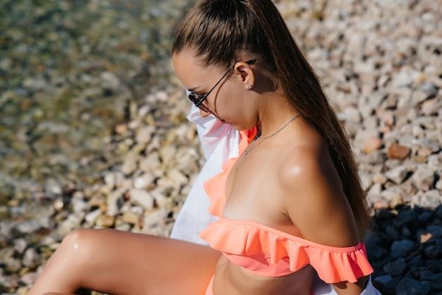 晴れた日には、巨大な岩を背景に、メガネとビキニを着た美しい若い女性が海岸に座っています。観光と観光旅行。