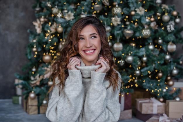 灰色のセーターを着た美しい若い女性。おもちゃ、ライトとクリスマスツリーの背景。