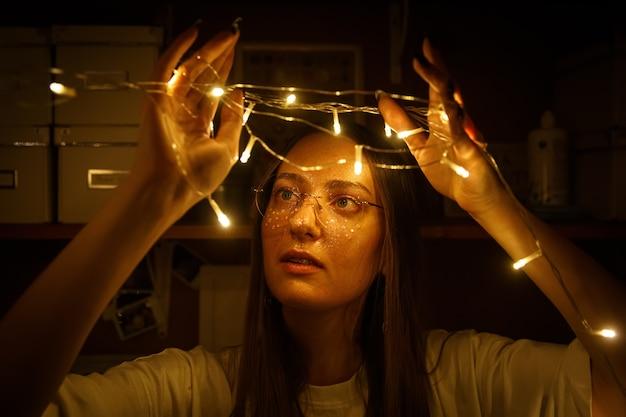 Красивая молодая женщина в круглых очках с блеском вокруг глаз держит в руках гирлянды огней.