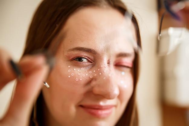 ピンクの星が彼女の目の周りにきらめく丸いメガネの美しい若い女性