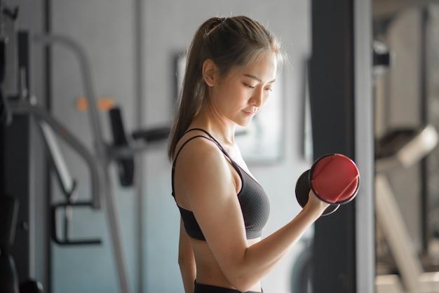 ジムでダンベル、健康的なライフスタイル、スポーツ、トレーニング、ウェルネス、スポーツの概念で運動するスポーツウェアの美しい若い女性