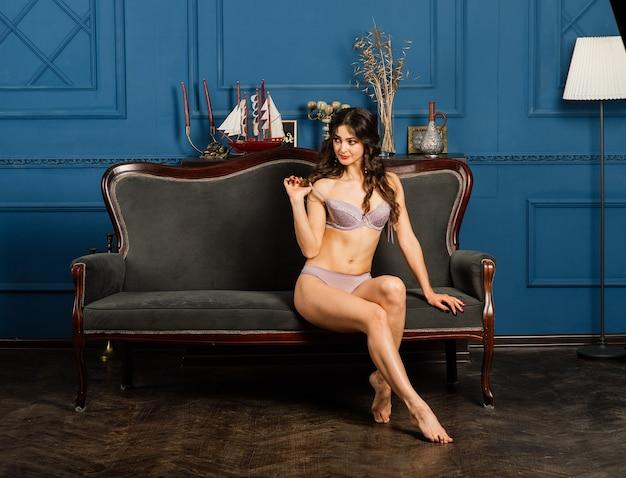 속옷을 입은 아름다운 젊은 여성이 침대에 반쯤 앉아 있습니다. 신부의 아침 개념.