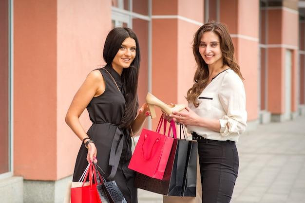 美しい若い女性がベージュの靴を持って、屋外のショッピングモールの近くに立っているガールフレンド、靴屋の近くに紙袋を持った2人のガールフレンド、買い物中毒者のコンセプトにそれを見せています
