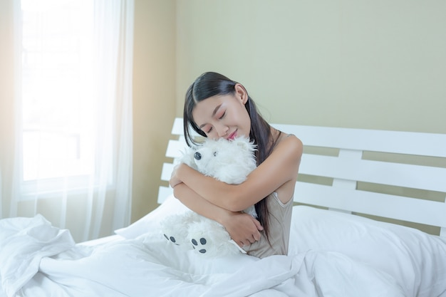 아름다운 젊은 여자가 자고 집에서 침실에서 알람 시계.