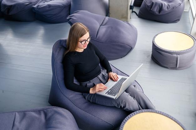 Красивая молодая женщина-менеджер сидит с ноутбуком на мягком пуфе возле панорамного окна. девушка-бизнесмен работает над новым проектом