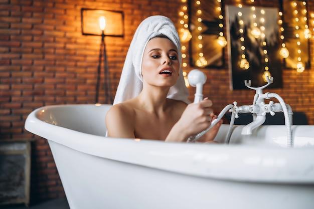 ポーズをとる美しい若い女性。頭にタオルを持って白いお風呂に横たわっている女性。黄色の花輪と赤レンガの壁