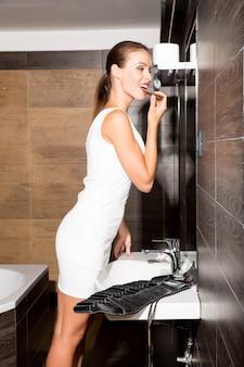 バスルームで化粧をして外出の準備をしている美しい若い女性。
