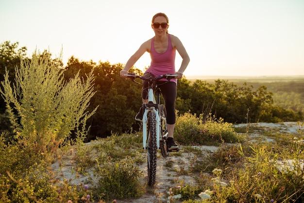Красивая молодая женщина катается на велосипеде в день природы