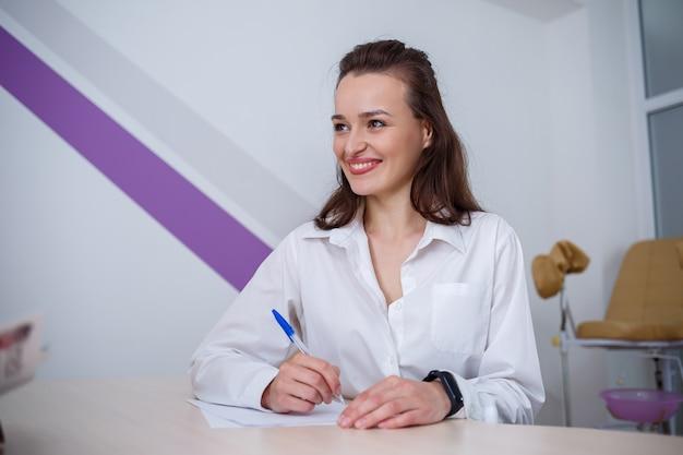 Красивая молодая женщина сидит за столом и подписывает важные документы.