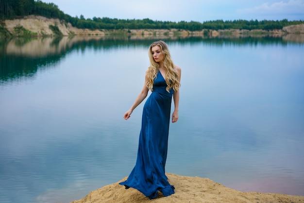 Красивая молодая женщина, стоящая у озера