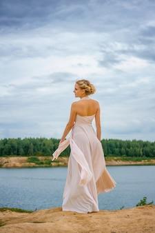 Красивая молодая женщина стоит в красивом платье на скале