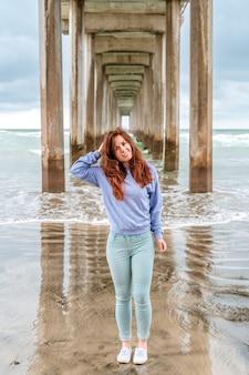 Красивая молодая женщина стоит под пирсом ла-хойя в пасмурную погоду сан-диего, калифорния