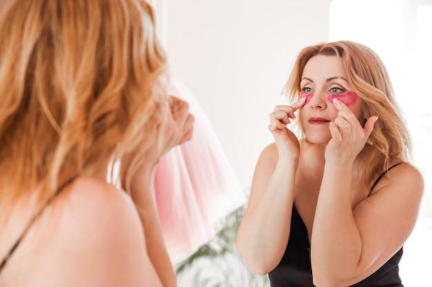 Красивая молодая женщина достает из упаковки розовые пятна и накладывает их под глаза