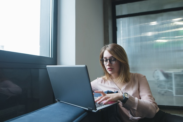 아름 다운 젊은 여자는 사무실에서 소파에 노트북을 사용합니다.