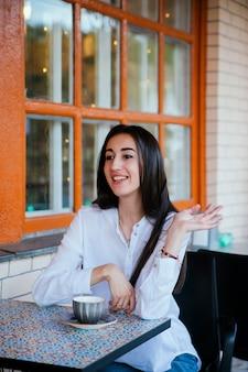 カフェのテーブルで通りすがりの人に手を振る美しい若い女性。若いかわいい女の子が注文したいと思っています。