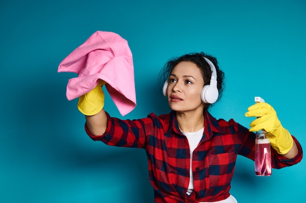 ヘッドフォンと黄色のゴム手袋を身に着けている美しい若い女性は、片方の手に洗剤のボトルを持ち、もう片方の手に掃除用ぼろきれを持っています