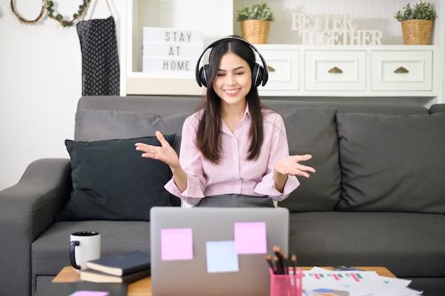 ヘッドセットを着ている美しい若い女性は、自宅のコンピューター、ビジネス技術コンセプトを介してビデオ会議通話を行っています。