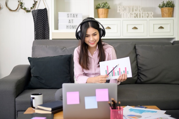 Красивая молодая женщина в наушниках делает видеоконференцию через компьютер дома во время пандемии коронавируса