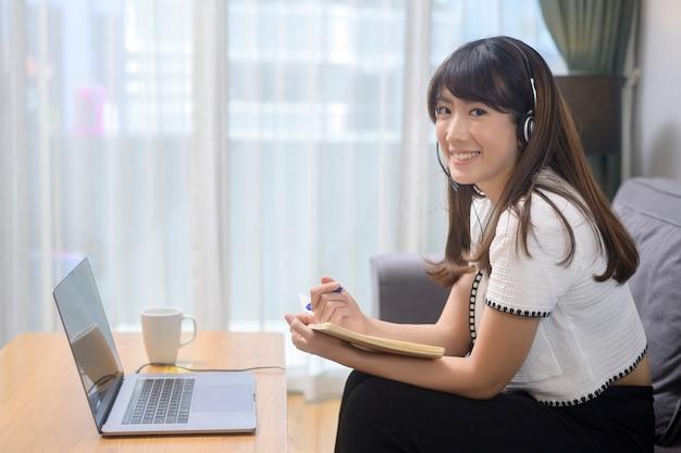 헤드셋을 쓴 아름다운 젊은 여성이 집에서 컴퓨터를 통해 화상 회의를 하고 있다