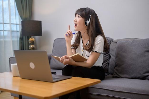 Красивая молодая женщина в наушниках делает видеоконференцию через компьютер дома