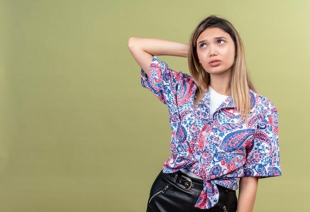 ペイズリー柄のシャツを着て、緑の壁を見上げながら頭に手をつないで考える美しい若い女性