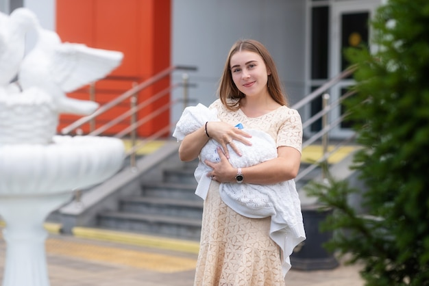 Красивая молодая женщина, недавно родившая ребенка, счастлива держит его на руках